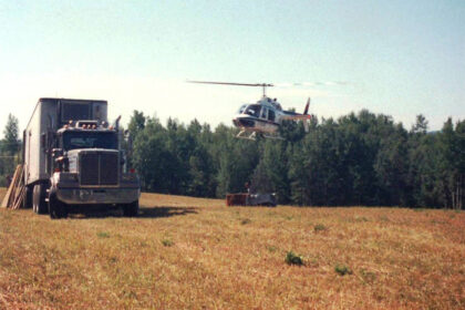 An old photo of a truck and helicopter.
