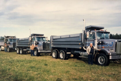 An older colour photo of three Michell team members posing next to their trucks, which are parked in single file.