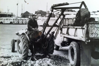 A black-and-white photo captures a man operating machinery.