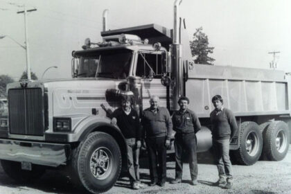 A black-and-white photo depicts Michell team members posing in front of a truck.