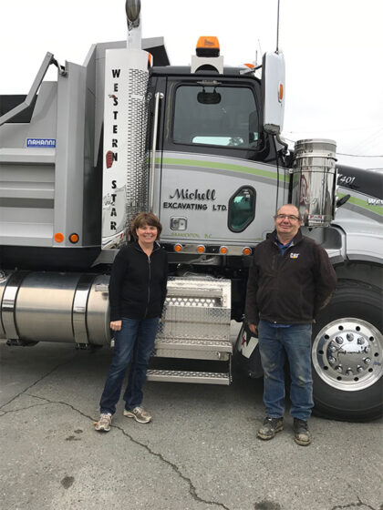 Two Michell team members pose in front of their truck.